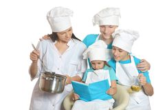 Mother and children cooking. Cheerful mother and children in chef uniforms cooking stock photo