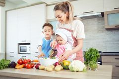 Mother and children are cooking in the kitchen royalty free stock images