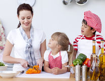 Mother and children cutting peppers in kitchen Royalty Free Stock Image