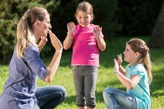Mother with children daughters doing dance exercise outdoors Stock Photography