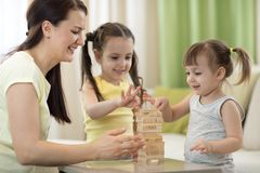 Mother and her little daughters are playing with board game. Mother and children daughters are playing with board game Royalty Free Stock Photos