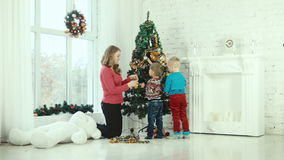 Mother and children decorate the Christmas tree stock video footage