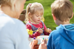 Mother And Children Decorating Easter Eggs. On Table Outdoors Stock Photo