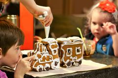 Mother and children decorating gingerbread Christmas train at home kitchen table. Mother and children decorating gingerbread Christmas steam train at home Stock Photo