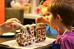 Mother and children decorating gingerbread Christmas train at home kitchen table. Mother and children decorating gingerbread Christmas steam train at home Royalty Free Stock Photography