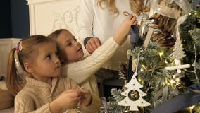 Mother and children decorating Xmas tree in beautiful family living room with fireplace. royalty free stock photography