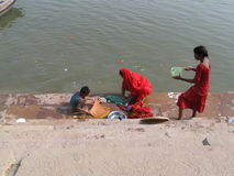 Mother and children doing laundry Assi Ghat Varanasi India. A typical day on the ghat in Varanasi, India, on the bank of the Ganges River. A woman with her son stock images