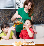 Mother with children drink juice stock photos