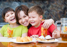 Mother with children drink juice Stock Image