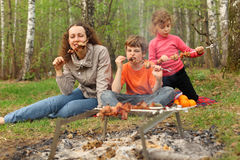 Mother and children eat grilled shish kebab Stock Image
