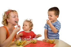 Mother and children eating fruit salad royalty free stock photos