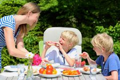 Mother with children eating outdoors Royalty Free Stock Photos