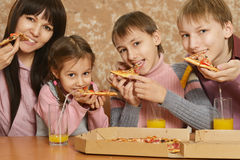 Mother with children eating pizza Stock Photos