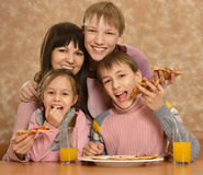 Mother with children eating pizza Stock Image