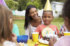 Mother With Children Enjoying Outdoor Birthday Party Together Royalty Free Stock Image