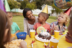 Mother With Children Enjoying Outdoor Birthday Party Together Stock Images