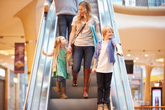 Mother And Children On Escalator In Shopping Mall. Happy Mother And Children On Escalator In Shopping Mall Holding Hands Royalty Free Stock Photo