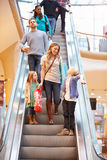 Mother And Children On Escalator In Shopping Mall. Holding Bags Smiling At Each Other Stock Images