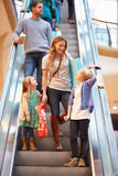Mother And Children On Escalator In Shopping Mall. Talking To Each Other Stock Images