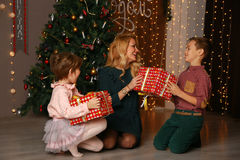 Mother and children exchanging and opening Christmas presents. Royalty Free Stock Photos