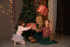 Mother and children exchanging and opening Christmas presents. Stock Photo