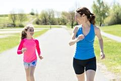 Mother with children girl sport running together outside. A mother with children girl sport running together outside stock photography