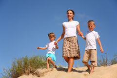 Mother with children goes on sand Stock Photos