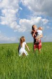 Mother and children in green field Stock Photography