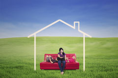 Mother and children on green field with dream house. Mother and children enjoying on red sofa with dream house picture outdoor Stock Photo