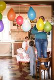 Mother with children hang colorful balloons for birthday party i. N her home, mother standing on the chair hangs balloons at the door Royalty Free Stock Photo