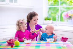 Mother and children having breakfast Royalty Free Stock Photos