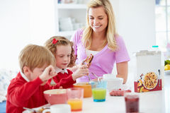 Mother And Children Having Breakfast In Kitchen Together royalty free stock photos