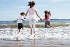 Mother And Children Having Fun On Beach Holiday Royalty Free Stock Image