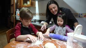 Mother and children having fun kneading dough at home stock video footage