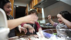 Mother and children having fun playing with flour stock video footage