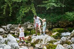 Mother with children having fun, playing by a mountain creek in summer royalty free stock photography