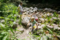 Mother with children having fun, playing by a mountain creek in summer. Outdoor lifestyle, positive parenting, childhood experience concept stock photos