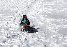 Mother and children having fun on the sled hill Stock Photo