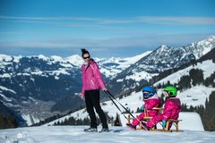 Mother and children having fun on sledge with panoramatic view of Alps mountains. Active mom and toddler kid with safety helmet. Winter sport for family royalty free stock image