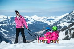 Mother and children having fun on sledge with panoramatic view of Alps mountains. Active mom and toddler kid with safety helmet. Winter sport for family royalty free stock photography