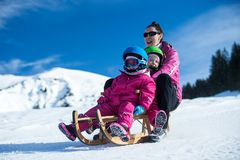 Mother and children having fun on sledge with panoramatic view of Alps mountains. Active mom and toddler kid with safety helmet. Winter sport for family stock photos