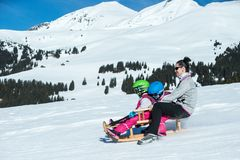 Mother and children having fun on sledge with panoramatic view of Alps mountains. Active mom and toddler kid with safety helmet. Winter sport for family stock photo