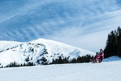 Mother and children having fun on sledge with panoramatic view of Alps mountains. Active mom and toddler kid with safety helmet. Winter sport for family royalty free stock images