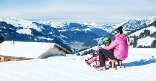 Mother and children having fun on sledge with panoramatic view of Alps mountains. Active mom and toddler kid with safety helmet. Winter sport for family royalty free stock photos