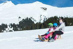 Mother and children having fun on sledge with panoramatic view of Alps mountains. Active mom and toddler kid with safety helmet. Winter sport for family royalty free stock photo