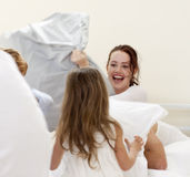 Mother and children having a pillow fight Royalty Free Stock Photography