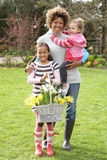 Mother And Children Holding Basket Of Daffodils Stock Photos