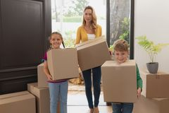 Mother and children holding cardboard boxes in a comfortable home stock photos