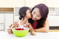 Mother and children in kitchen. Young mother with her children in the kitchen and helping her son to drink Royalty Free Stock Photography