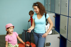 Mother with children in left-luggage office Stock Photos